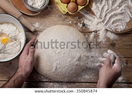 Male baker prepares bread. Male baker sprinkle the dough with flour. Making bread. Top view. Rustic style - stock photo