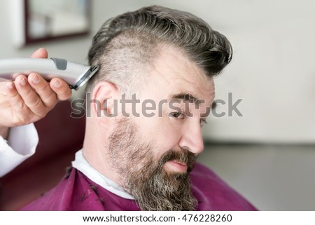Male barber makes a mohawk hairstyle using clipper of a adult man with beard