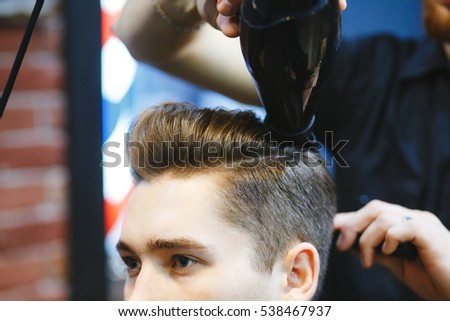 Male barber makes hair styling using a dryer of a young man.