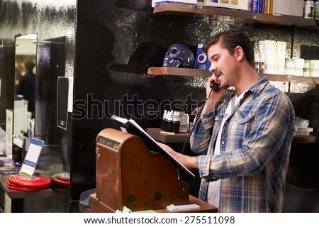Male Barber Standing By Cash Register Taking Booking - stock photo