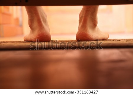 male bare feet photo from under the bed, selective focus