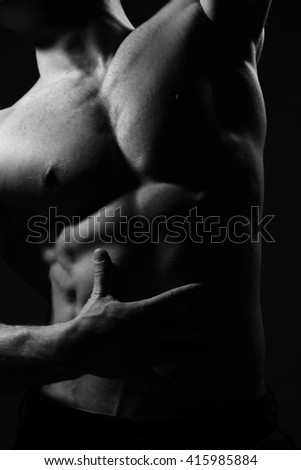 Male bare torso and sexy muscular body of young handsome man posing in studio, black and white