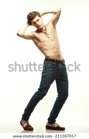 Male beauty & Blue jeans concept. Handsome male model in trendy jeans and red loafers with perfect muscular body posing over white background. Leather accessories. Urban style. Full length portrait
