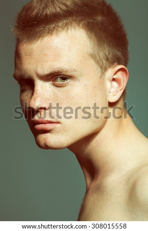 Male beauty concept. Close up portrait of handsome young fashion model posing over gray background. Trendy haircut. Freckles on face. Studio shot