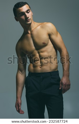 Male beauty concept. Fashionable and undressed young man in black classic trousers with stylish haircut posing over gray background. Perfect hair & skin. Vogue style. Close up. Studio shot