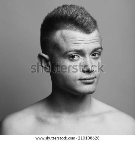 Male beauty concept. Fashionable young man with stylish haircut over gray background. Skin with freckles. Surprised face. Wrinkles on forehead. Hipster style. Close up. Black & white studio shot - stock photo