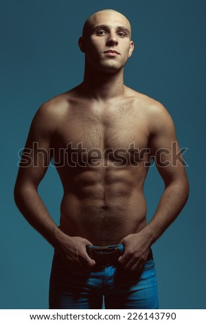 Male beauty concept. Handsome male model wearing blue jeans posing over blue background. Perfect skin, shaved head, hairy muscular body. Close up. Fashion studio portrait - stock photo
