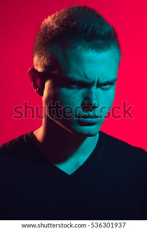 Male beauty concept. Pop-art portrait of young man with perfect haircut wearing black t-shirt over pink background. Avant-garde, disco style. Close up. Studio shot