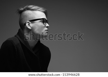 Male beauty concept. Portrait of a fashionable young man with stylish haircut wearing trendy glasses and sweater & posing over gray background. Perfect hair & skin. Hipster style. Close up. Copy-space