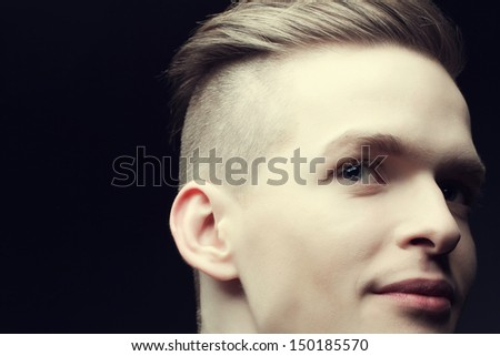 Male beauty concept. Portrait of a smiling handsome young man with stylish haircut posing over black background. Perfect hair & skin. Urban hipster style. Close up. Copy-space. Studio shot - stock photo