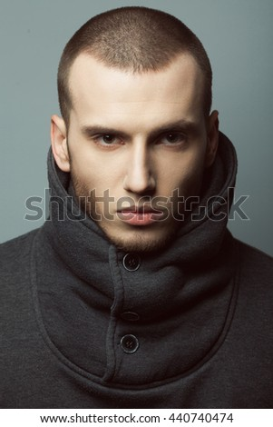 Male beauty concept. Portrait of brutal young man with short hair wearing gray sweatshirt with high collar and buttons posing over gray background. Modern street style. Close up. Studio shot - stock photo