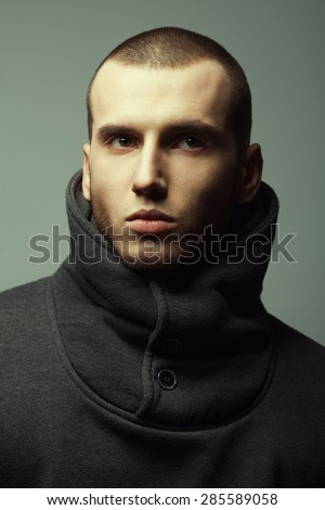Male beauty concept. Portrait of brutal young man with short hair wearing gray sweetshirt with high collar and posing over gray background. Modern street style. Close up. Studio shot - stock photo