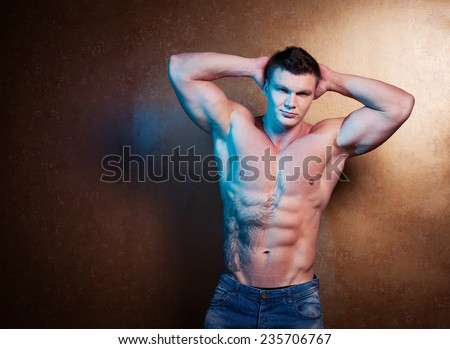 Male beauty concept. Portrait of fashionable and undressed young man in blue jeans with stylish haircut posing over gold background. Perfect hair & skin. Tough guy. Close up.  Tattoo.