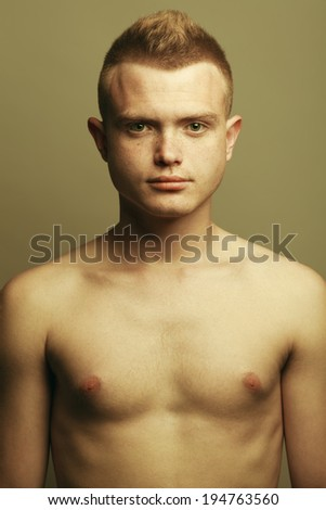 Male beauty concept. Portrait of fashionable and undressed young man with stylish haircut posing over mustard background. Perfect hair & skin. Hipster style. Close up. Studio shot - stock photo