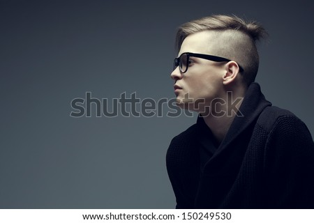 Male beauty concept. Portrait of fashionable young man with stylish haircut wearing trendy glasses and sweater, posing over gray background. Perfect hair & skin. Hipster style. Copy-space. Studio shot - stock photo