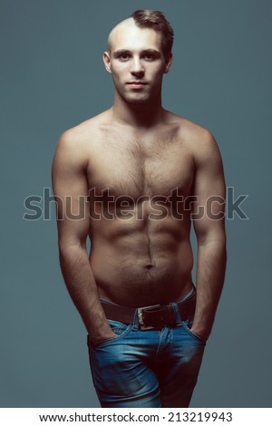 Male beauty concept. Portrait of handsome muscular male model in jeans with hands in pockets over gray background. Half-shaved or half-bald head and healthy clean skin. Fashion studio shot