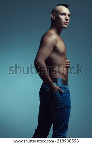 Male beauty concept. Portrait of hungry handsome muscular male model in jeans posing over blue background with hand in pocket. Shaved head with upright crest. Tough guy style. Copy-space. Studio shot - stock photo