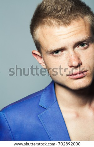 Male beauty concept. Portrait of young man with perfect haircut wearing blue classic jacket. Hollywood star style. Blue-eyed boy with blond hair. Close up. Studio shot
