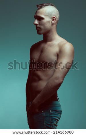 Male beauty concept. Profile portrait of handsome muscular male model in jeans with hands in pockets over gray background. Shaved head and healthy clean skin. Tough guy style. Fashion studio shot - stock photo