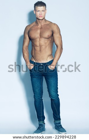 Male beauty & fashion concept. Full length portrait of handsome muscular male model in jeans posing over blue background. Blond hair and healthy clean skin. Studio shot - stock photo