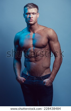 Male beauty & fashion concept. Portrait of handsome muscular male model in jeans posing over blue background. Blond hair and healthy clean skin. Studio shot - stock photo