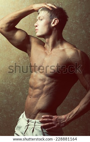 Male beauty & fashion concept. Profile portrait of handsome muscular male model in trendy summer pants posing over golden background. Blond hair and healthy clean skin. Studio shot - stock photo