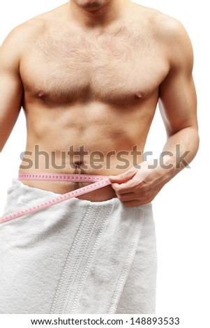Male beauty. Young man measuring waist diameter