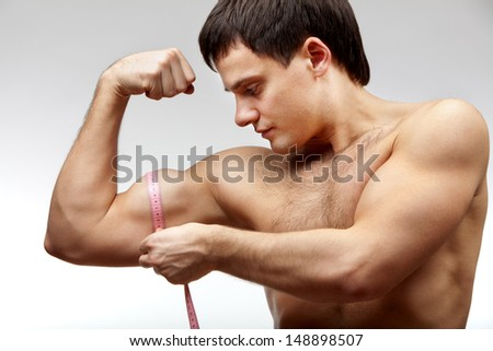 Male beauty. Young muscular man measuring bicep diameter