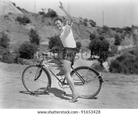 Male bicyclist waving - stock photo