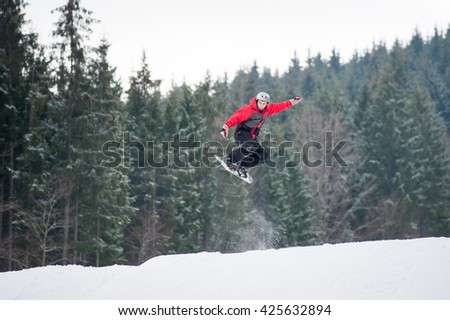 Male boarder on the snowboard jumping over the slope in winter with snowy slope and snow-covered firs in background, extreme sport