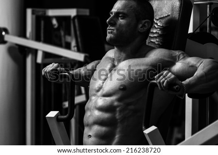Male Bodybuilder Doing Heavy Weight Exercise For Chest - stock photo