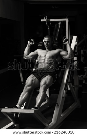 Male Bodybuilder Doing Heavy Weight Exercise For Legs - stock photo