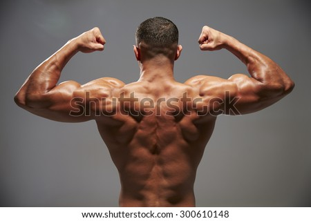 Male bodybuilder flexing his biceps, back view - stock photo