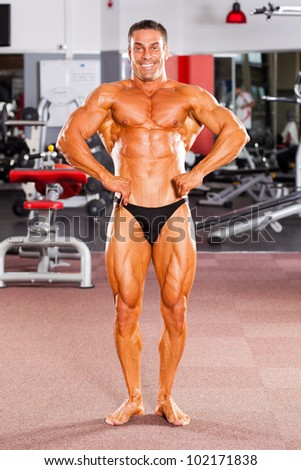 male bodybuilder flexing his muscle in gym - stock photo