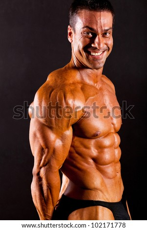male bodybuilder flexing muscle on black background - stock photo