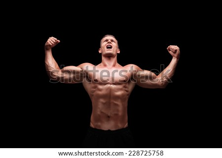 Male bodybuilder gesturing happiness on black background - stock photo
