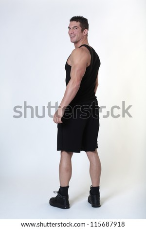 male bodybuilder looking over his shoulder back at camera with a big smile on his face - stock photo