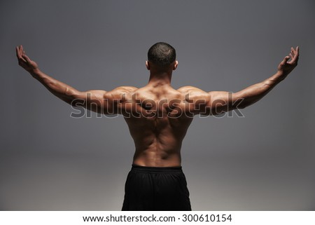 Male bodybuilder raising his arms, back view - stock photo