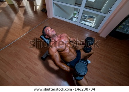 male bodybuilder resting after doing heavy weight exercise - stock photo