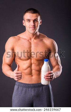 Male bodybuilder shows that milk is good. Concept of healthy food.