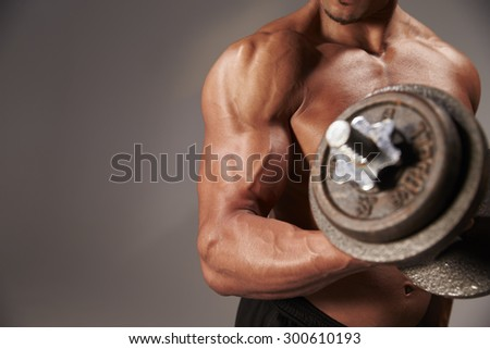 Male bodybuilder working out with a  heavy dumbbell, crop detail