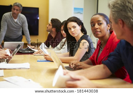 Male Boss Addressing Meeting Around Boardroom Table - stock photo