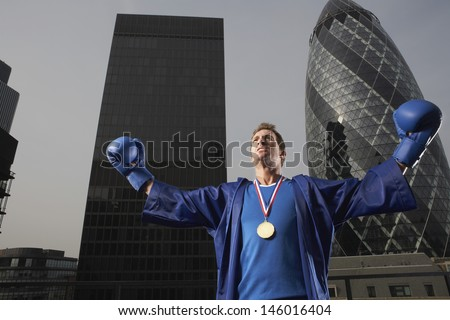 Male boxer wearing gold medal in front of downtown skyscrapers in London - stock photo
