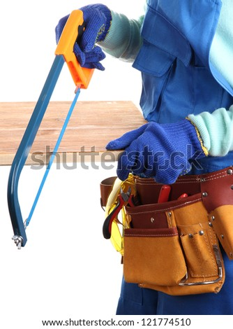 Male builder in blue overalls sawing board isolated on white - stock photo