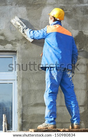 Male builder plastering exterior wall during industrial facade building with putty knife float - stock photo