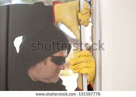 Male burglar with black hood, gloves and sunglasses trying to break in residential house, home,  through window, with copy space. - stock photo