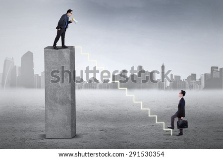 Male business leader standing on the bar and shouting to his subordinate with a megaphone - stock photo