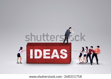 Male business leader with megaphone commanding his team to carry business ideas - stock photo