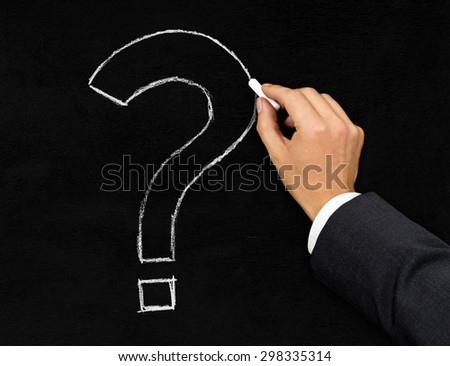 Male businessman drawing question mark with chalk on blackboard background - stock photo