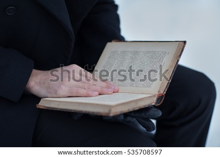 Male businessman is reading a book, placed her left hand on the page the winter on the street